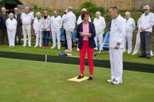 Ann egets some instruction on how to bowl from coach David